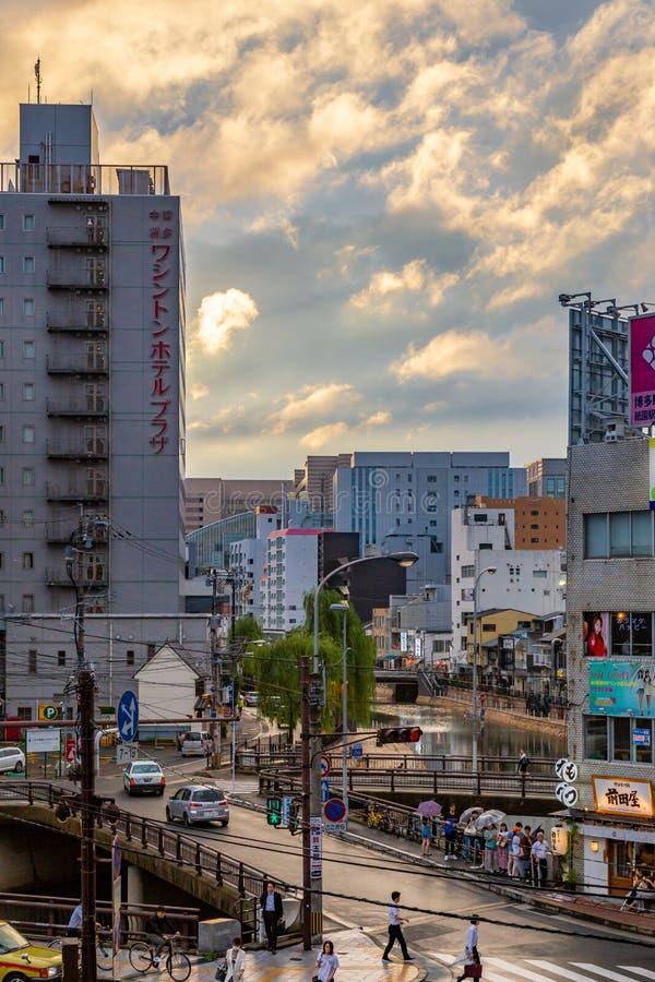 Les piétons se promènent dans les rues animées de Fukuoka, au Japon, dans une soirée pluvieuse photos libres de droits