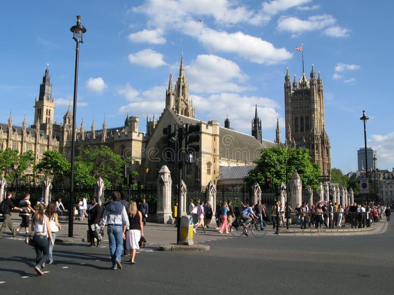 Les piétons traversent la rue de pont sur le passage piéton près des Chambres de palais de Westminster du Parlement à Londres, R- photographie stock libre de droits