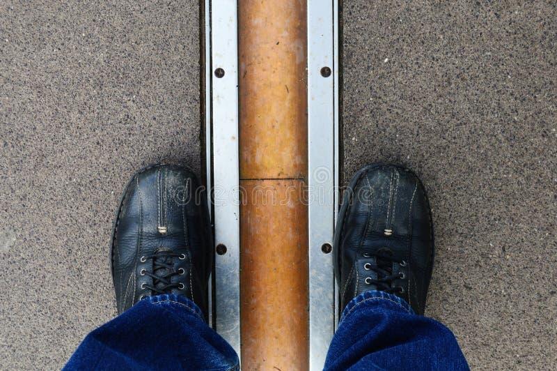 Les pieds à cheval sur le méridien principal rayent à Greenwich photos stock