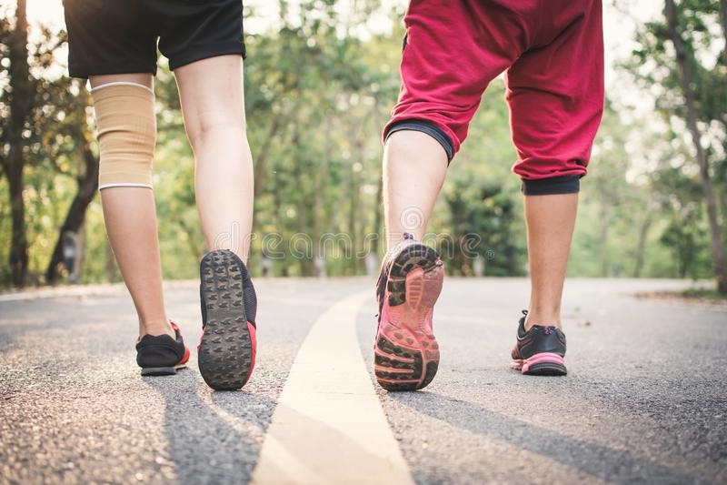 Les pieds équipent et femme courant sur la route pour la santé image libre de droits