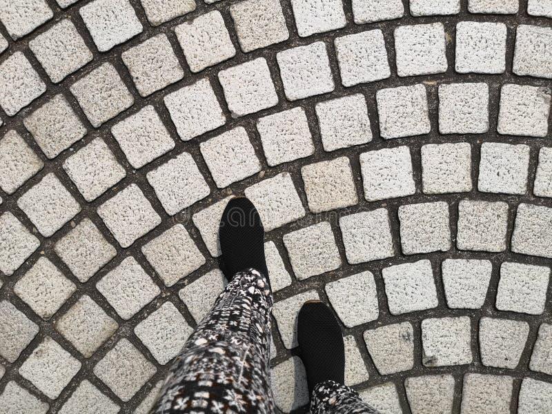 Les pieds d'une personne font attention aux chaussures noires marchant sur le modèle gris de courbe de pavé rond pavant sur une r photo stock