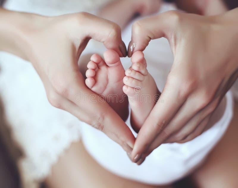 Les pieds de bébé dans la maman remet les tenir dans la forme de coeur photos libres de droits