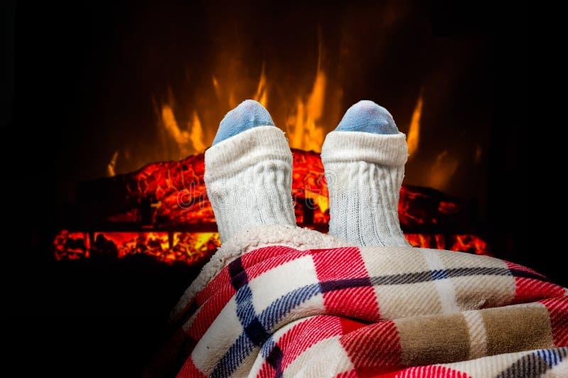 Les pieds de chauffage de femme dans les chaussettes de laine s'approchent de la cheminée image stock