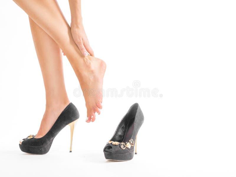 Les pieds de chaussure de talons hauts font souffrir, d'isolement sur le fond blanc La femme a enlevé ses chaussures de fatigue d photographie stock