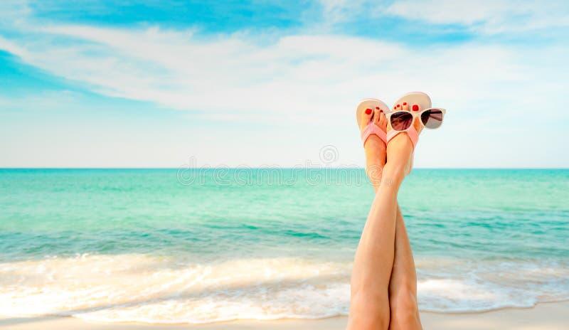 Les pieds de femme de partie supérieure et la pédicurie rouge portent les sandales roses, lunettes de soleil au bord de la mer Je photos stock