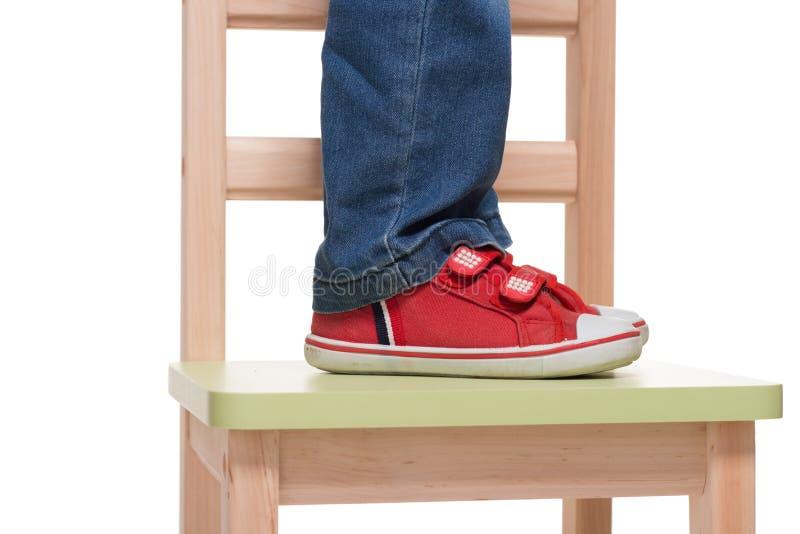 Les pieds de l'enfant restant sur la petite présidence photo stock