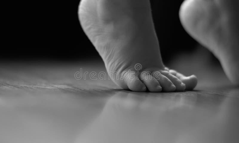 Les pieds de l'enfant se tenant sur la pointe des pieds noirs et blancs images stock