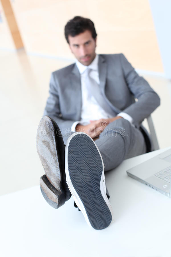 Les pieds de l'homme d'affaires sur la table image stock