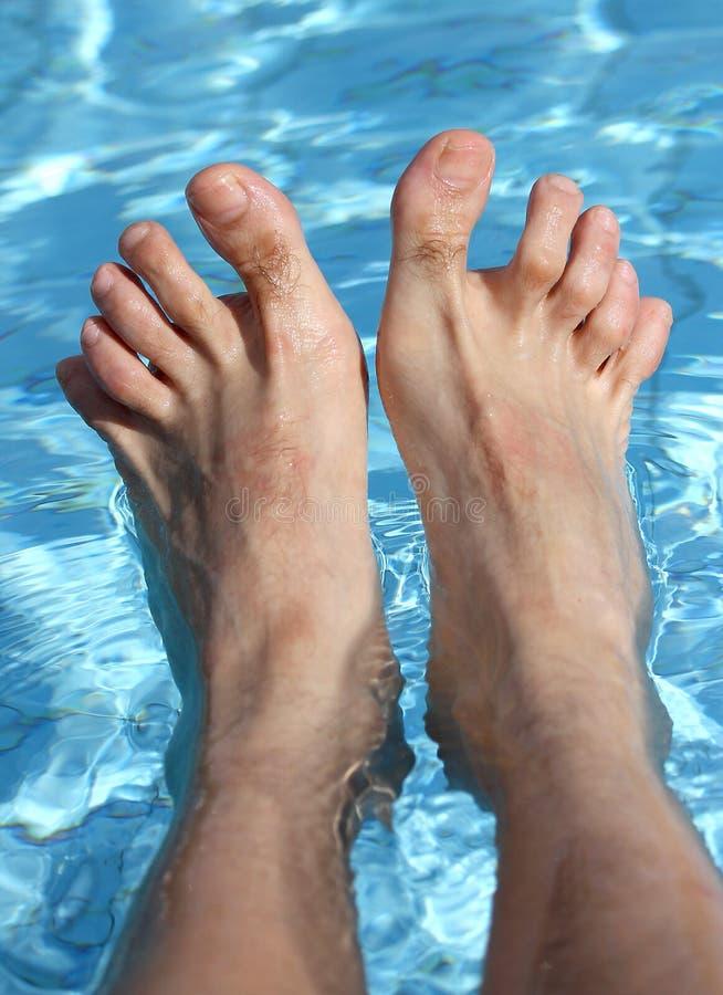 Les pieds de l'homme sur la baignoire d'une piscine de détente image libre de droits
