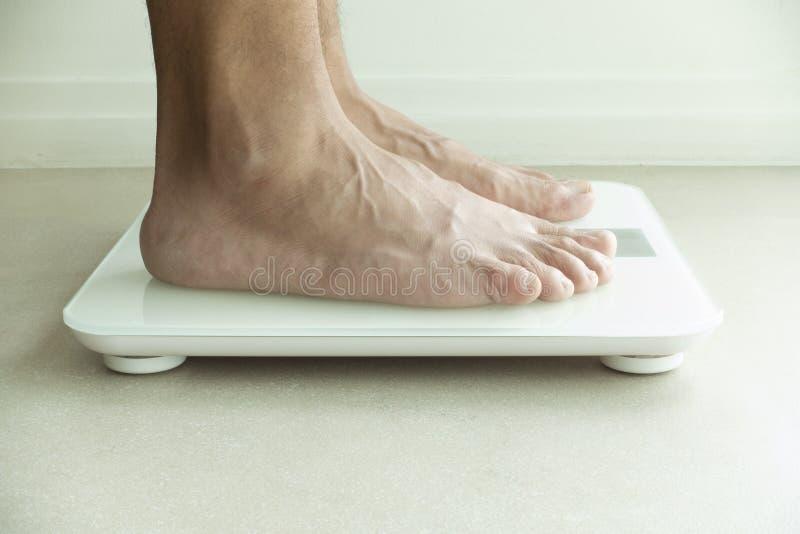 Les pieds de l'homme sur le poids vérifiant la machine photo libre de droits