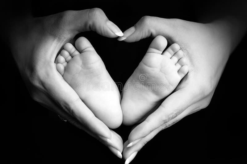 Les pieds de la chéri dans des paumes de la maman photo libre de droits