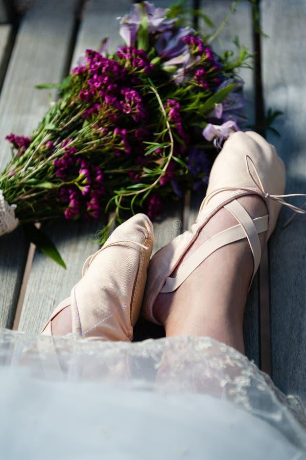 Les pieds de la femme dans des pantoufles de ballet avec le bord de dentelle et un bouquet voisin des wildflowers photos stock