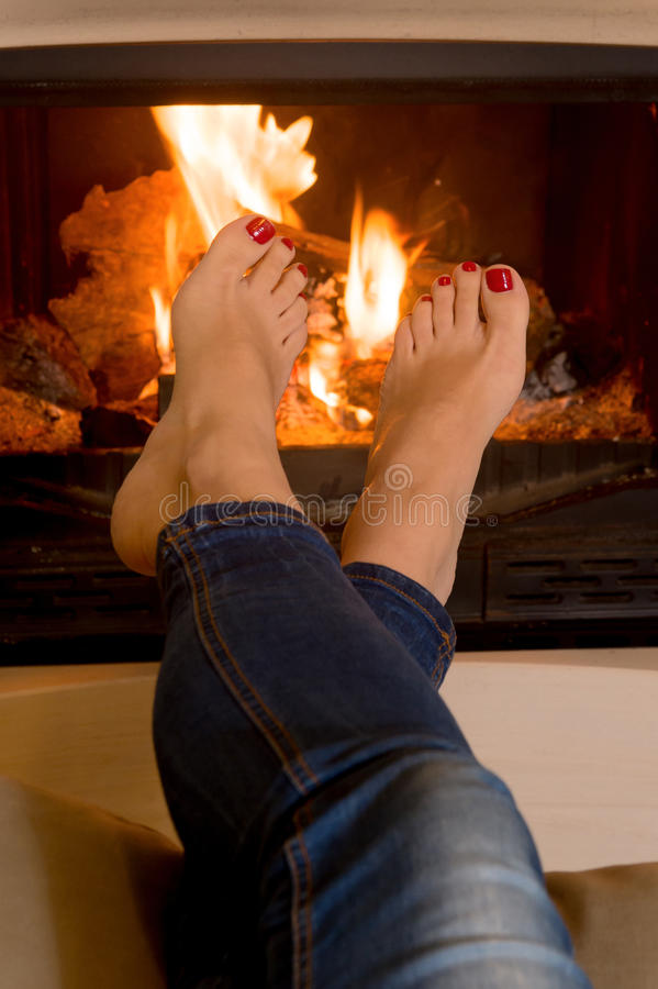 Les pieds de la femme devant un feu photo stock