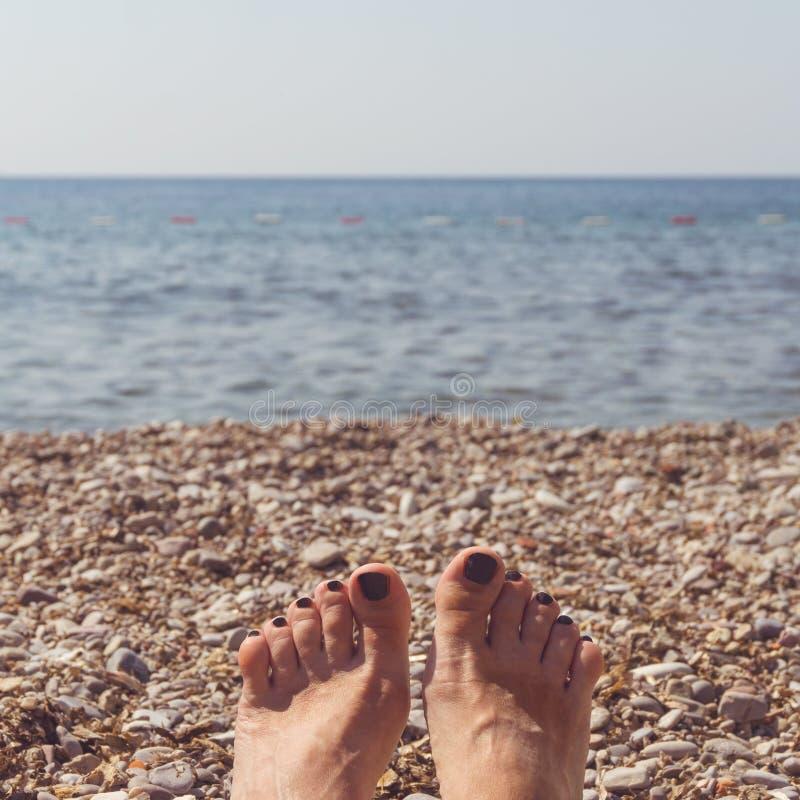 Les pieds des femmes avec les manucures noires sur la plage photographie stock
