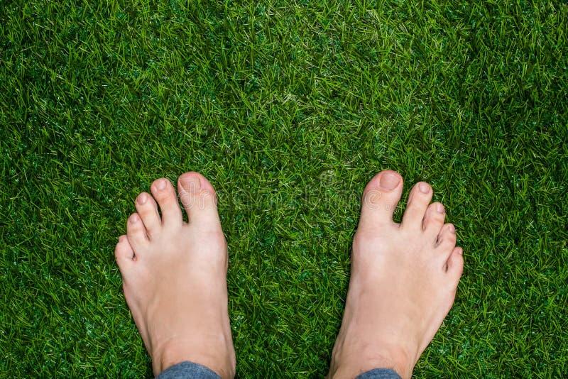 Les pieds des hommes se levant sur la fin d'herbe photo libre de droits