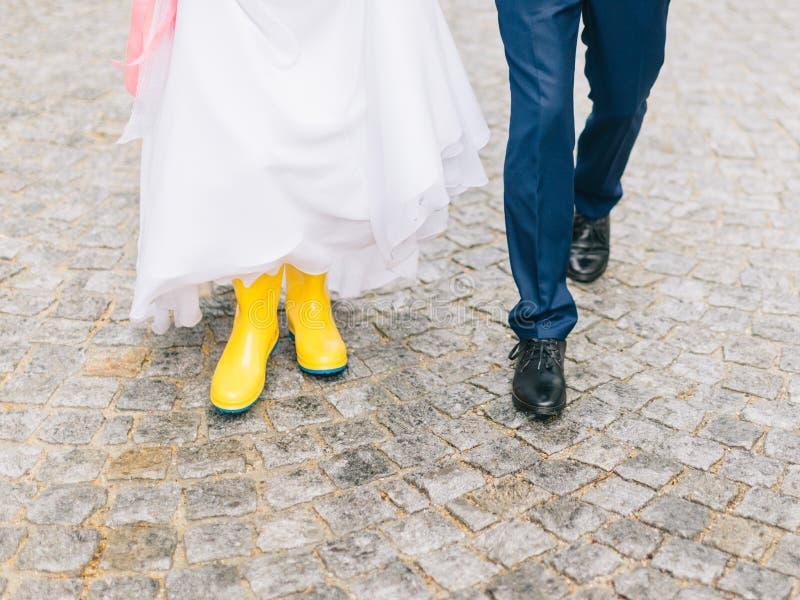 Les pieds des jeunes mariés marchent par temps pluvieux photos stock