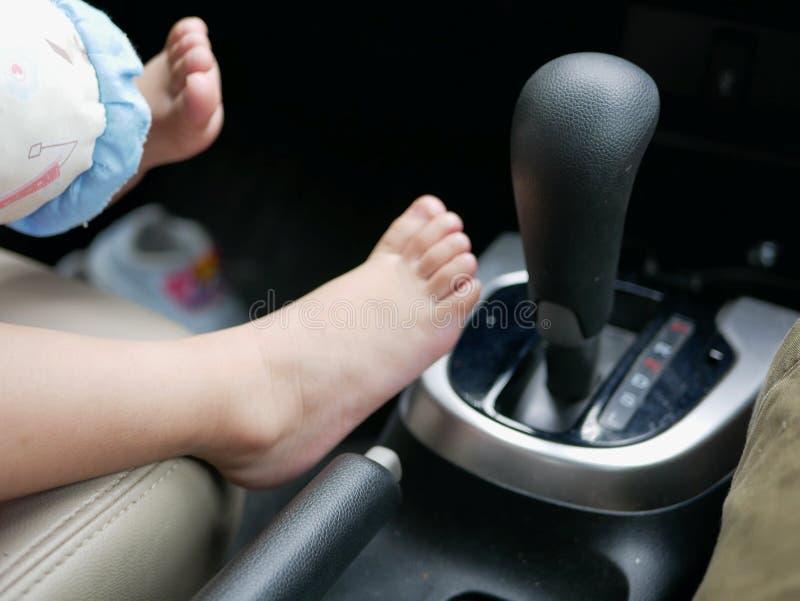 Les pieds du bébé étant mis à côté d'une vitesse d'une voiture motrice image libre de droits