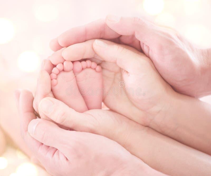 Les pieds du bébé nouveau-né minuscule en plan rapproché des mains du parent Famille heureux photos libres de droits
