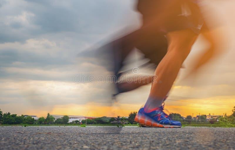 Les pieds du coureur, coureur de tir de plan rapproché de coureur brouillé par mouvement courant rapidement la lumière du soleil  image stock