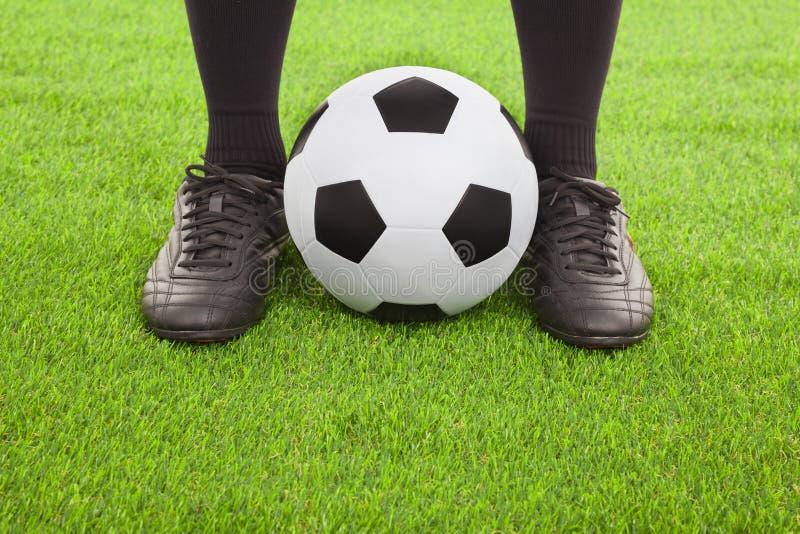 Les pieds du footballeur avec la boule photographie stock