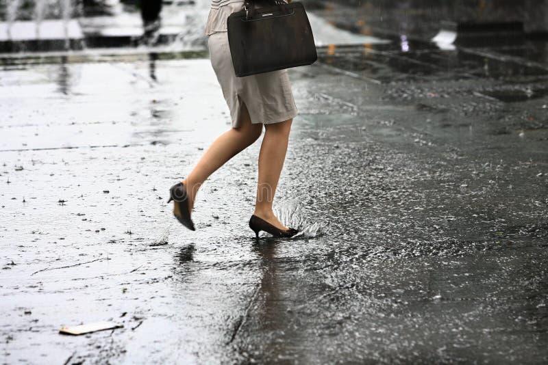 Les pieds femelles avec des chaussures de talons marchent sur l'eau photo stock