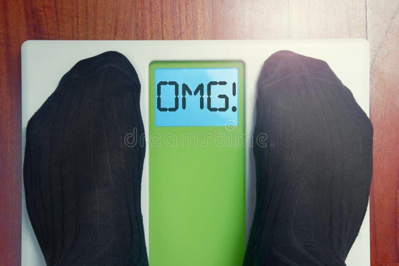 Les pieds masculins de plan rapproché mesurent OMG oh mon Dieu au matin image stock
