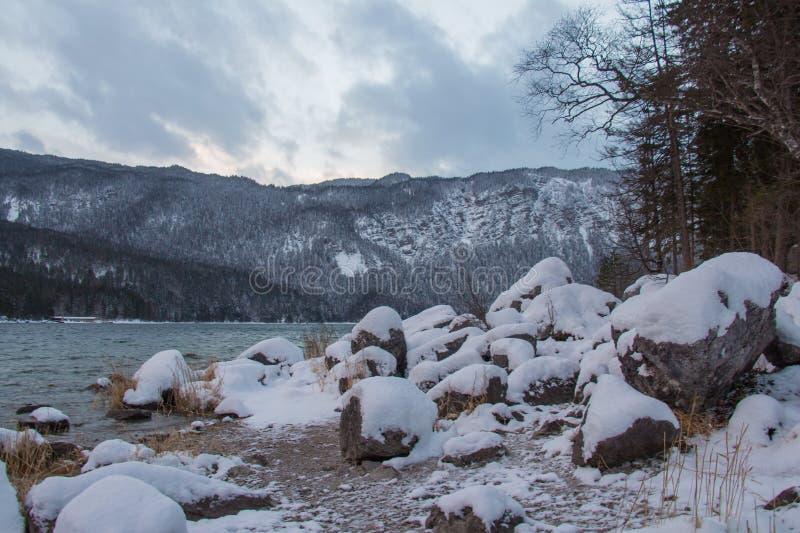 Les pierres au lac Eibsee étayent avec des montagnes sur le fond dans l'horaire d'hiver bavaria l'allemagne images libres de droits