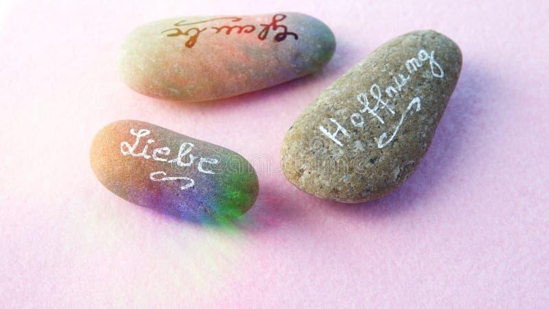 Les pierres avec des mots allemands pour l'amour, croient et espèrent sur le dos de rose photographie stock libre de droits