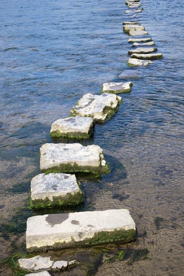 Les pierres de progression de granit traversent une rivière photos stock