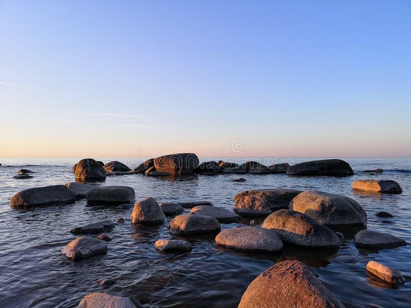 Les pierres se situent dans les eaux côtières en mer baltique, Lettonie Coucher du soleil d'été photo stock
