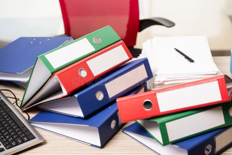 Les piles de reliures de bureau sur le bureau photographie stock