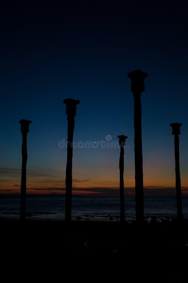 Les piliers accouplent le support avec la vue de coucher du soleil sur la plage de Tedys photographie stock libre de droits