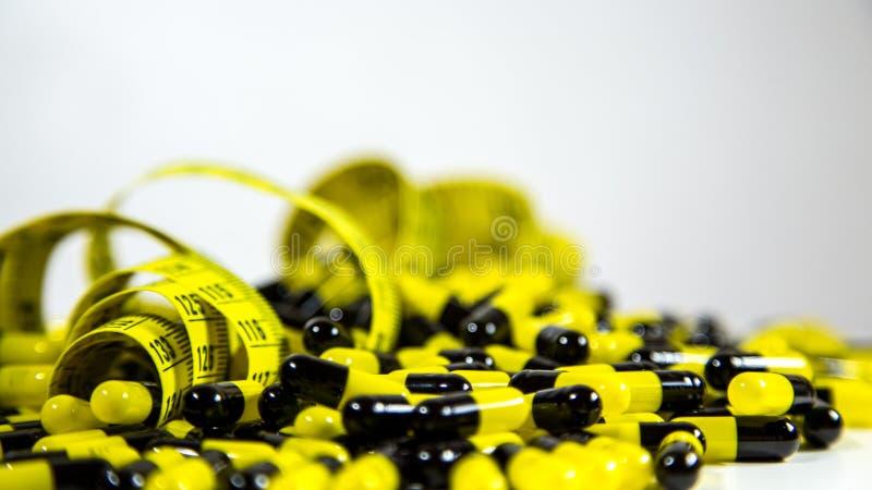 Les pilules avec la bande de mesure sur le fond blanc, représentent l'industrie de pilule de régime image stock