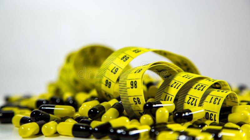 Les pilules avec la bande de mesure sur le fond blanc, représentent l'industrie de pilule de régime photographie stock