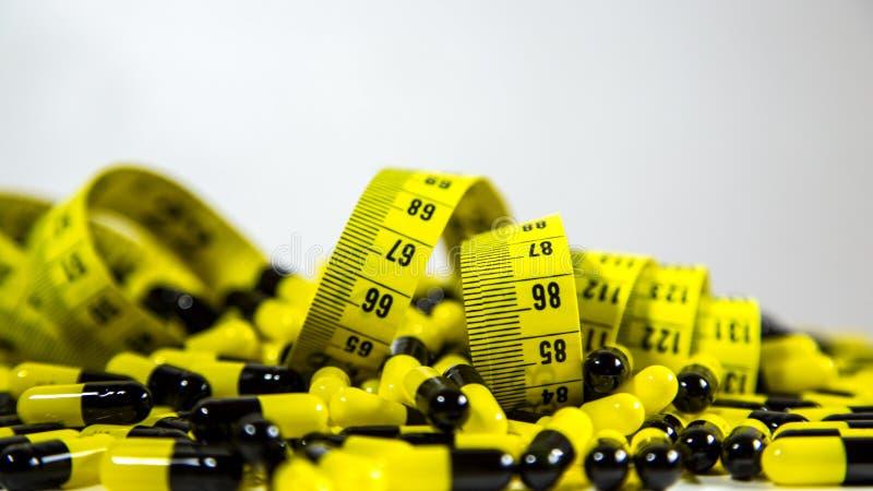 Les pilules avec la bande de mesure sur le fond blanc, représentent l'industrie de pilule de régime photographie stock libre de droits