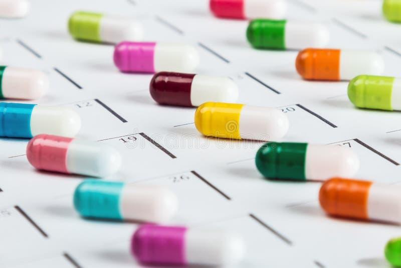 Les pilules sont de couleur différente sur le calendrier images stock