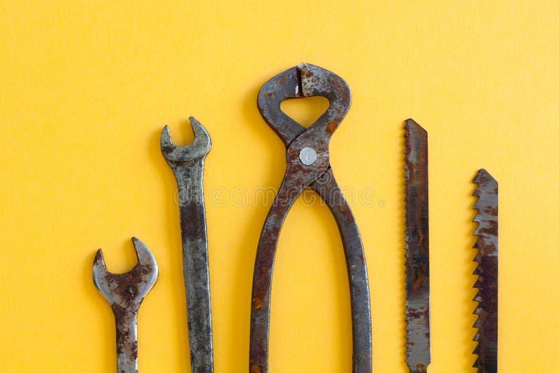 Les pinces rouillées de clés scie des lames sur le papier jaune L'instrument d'outils de bricolage de fer de vintage pour le serv photos stock