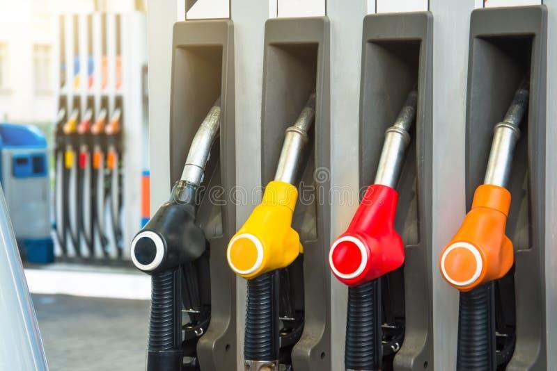 Les pistolets colorés d'essence pompent les becs remplissants, réapprovisionnant en combustible des stations service dans un serv images stock