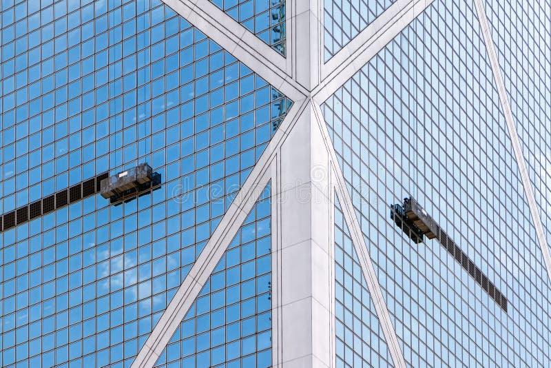 Les plates-formes de travail accrochant par des cordes du côté d'un gratte-ciel photographie stock libre de droits