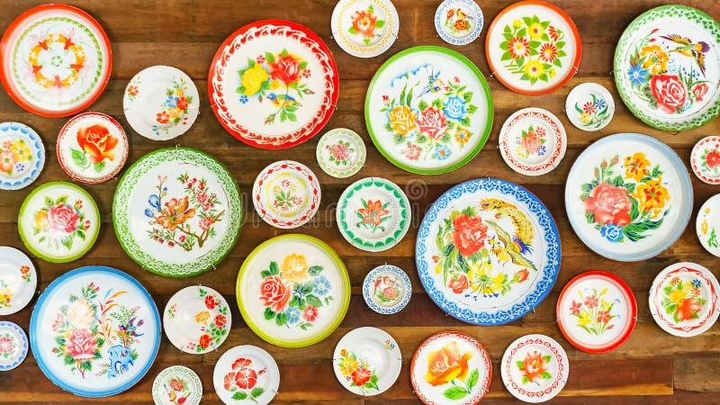 Les plats asiatiques colorés de style sur le mur en bois donnent au fond une consistance rugueuse, I image stock