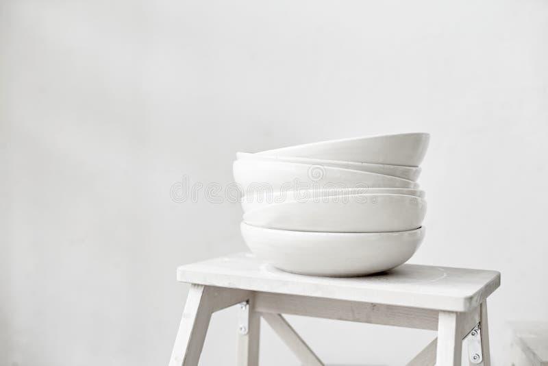 Les plats en céramique vides blancs se tiennent dans un support de pile sur un tabouret en bois, équipement de cuisine photo libre de droits