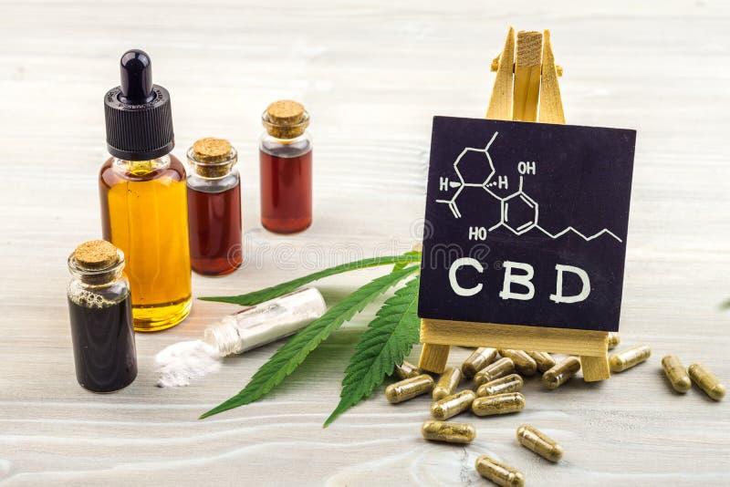 Les pleins huiles, capsules et cristaux de Cannabidiol CBD de spectre isolent avec le petit tableau noir avec le mot et la consti photo stock