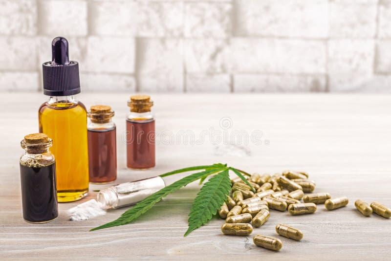 Les pleins huiles, capsules et cristaux de Cannabidiol CBD de spectre isolent sur le contexte en bois photographie stock libre de droits