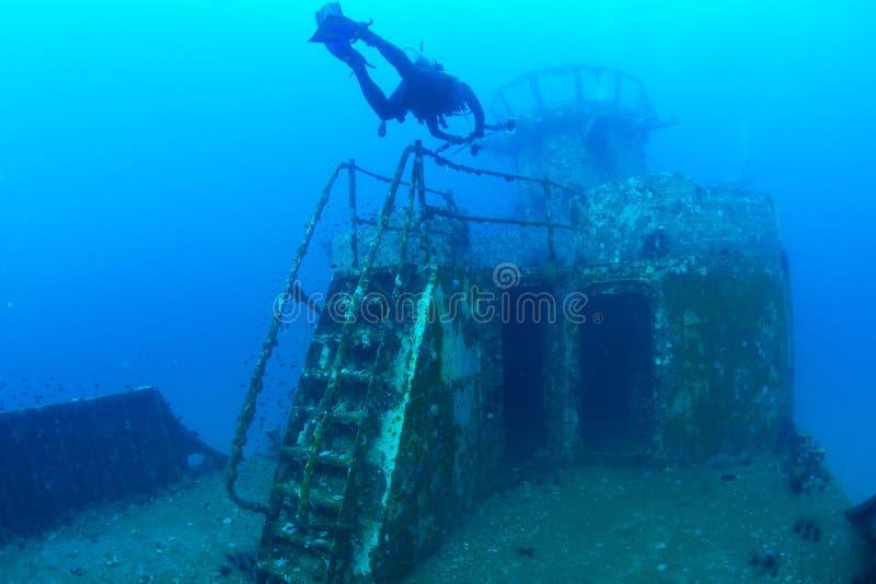 Les plongeurs explorant le bateau détruisent en mer tropicale image stock