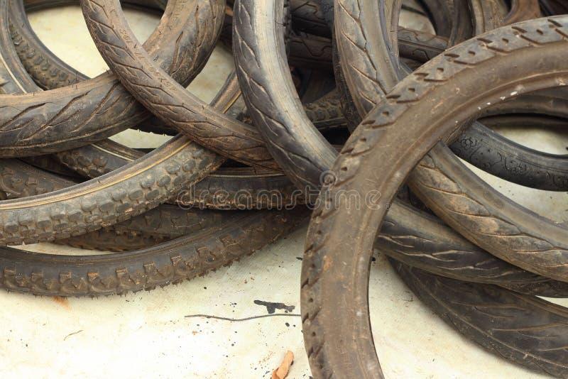 Les pneus de voiture d'occasion ont mis une pile sur le plancher image libre de droits