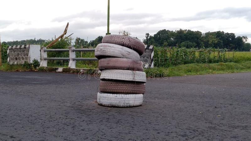 Les pneus de voiture empilent au milieu de la route image libre de droits