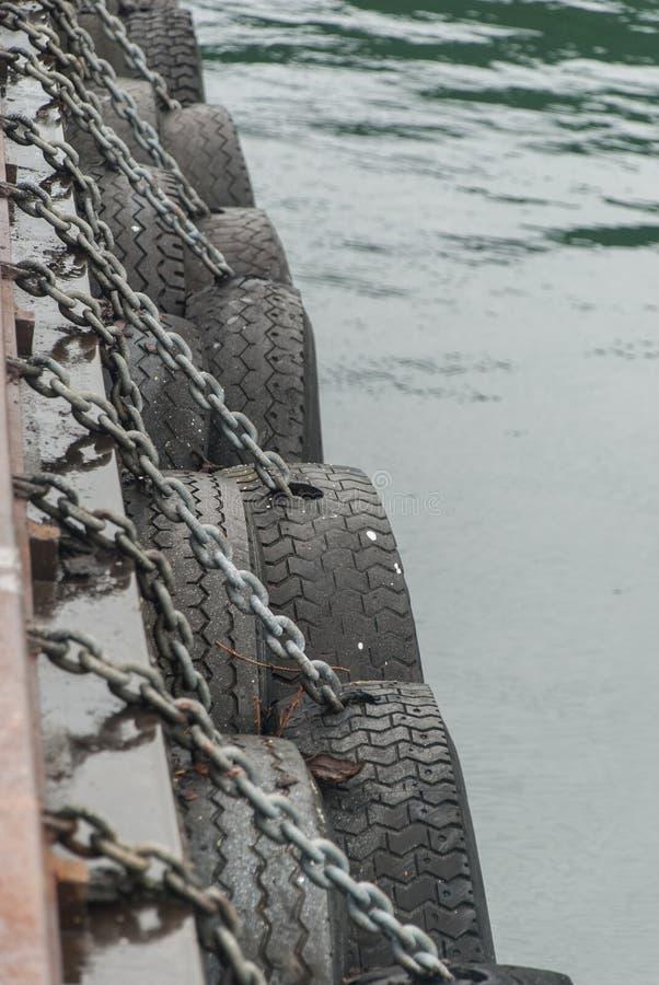 Les pneus en caoutchouc sur des chaînes sont le long de la couchette pour des bateaux image stock