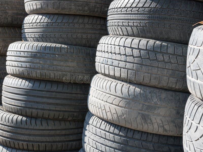 Les pneus utilis?s et vieux ont empil? un sur l'un autre ? c?t? du garage de magasin photos stock