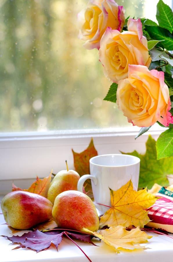 Les poires et les roses jaunes avec des feuilles d'érable s'approchent de la fenêtre image stock