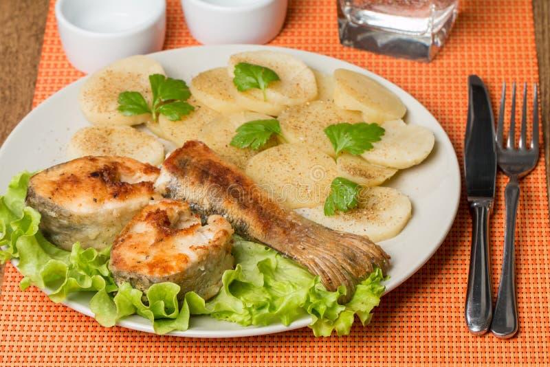 Les poissons blancs avec la pomme de terre sur le blanc plat photo stock